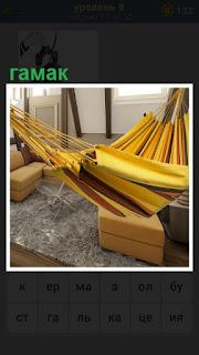 в комнате между креслами висит гамак желтого цвета