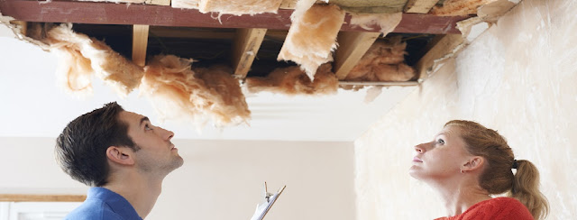 Stock photo of a male/female couple staring up at a ruined ceiling that shows exposed wood and insulation