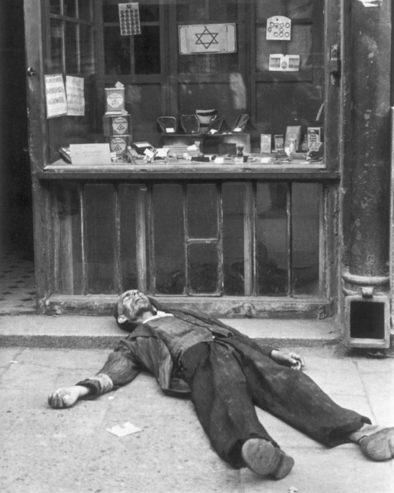 Dead man lies in front of a shop in the Warsaw ghetto.