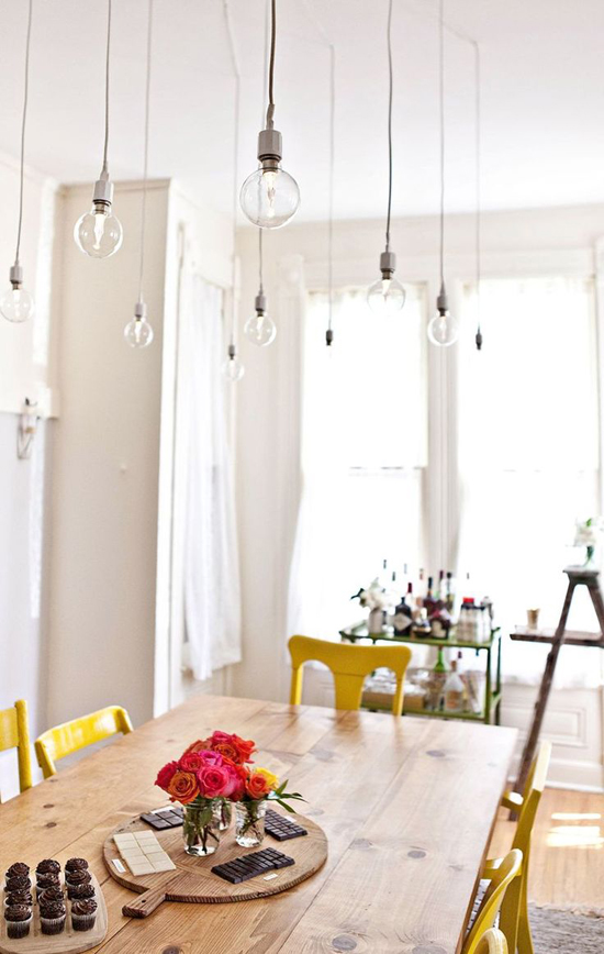 Happy dining room with bare bulb pendant lights by A Beautiful Mess