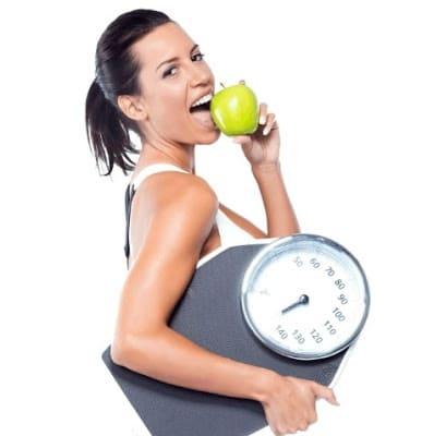 Mulher comendo maçã e segurando balança