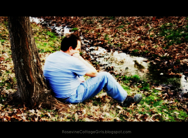 photo of man sitting by stream with blue jeans on and blue shirt leaning against a tree. | rosevinecottagegirls.com | 22 things you should know | @rosevine cottage girls