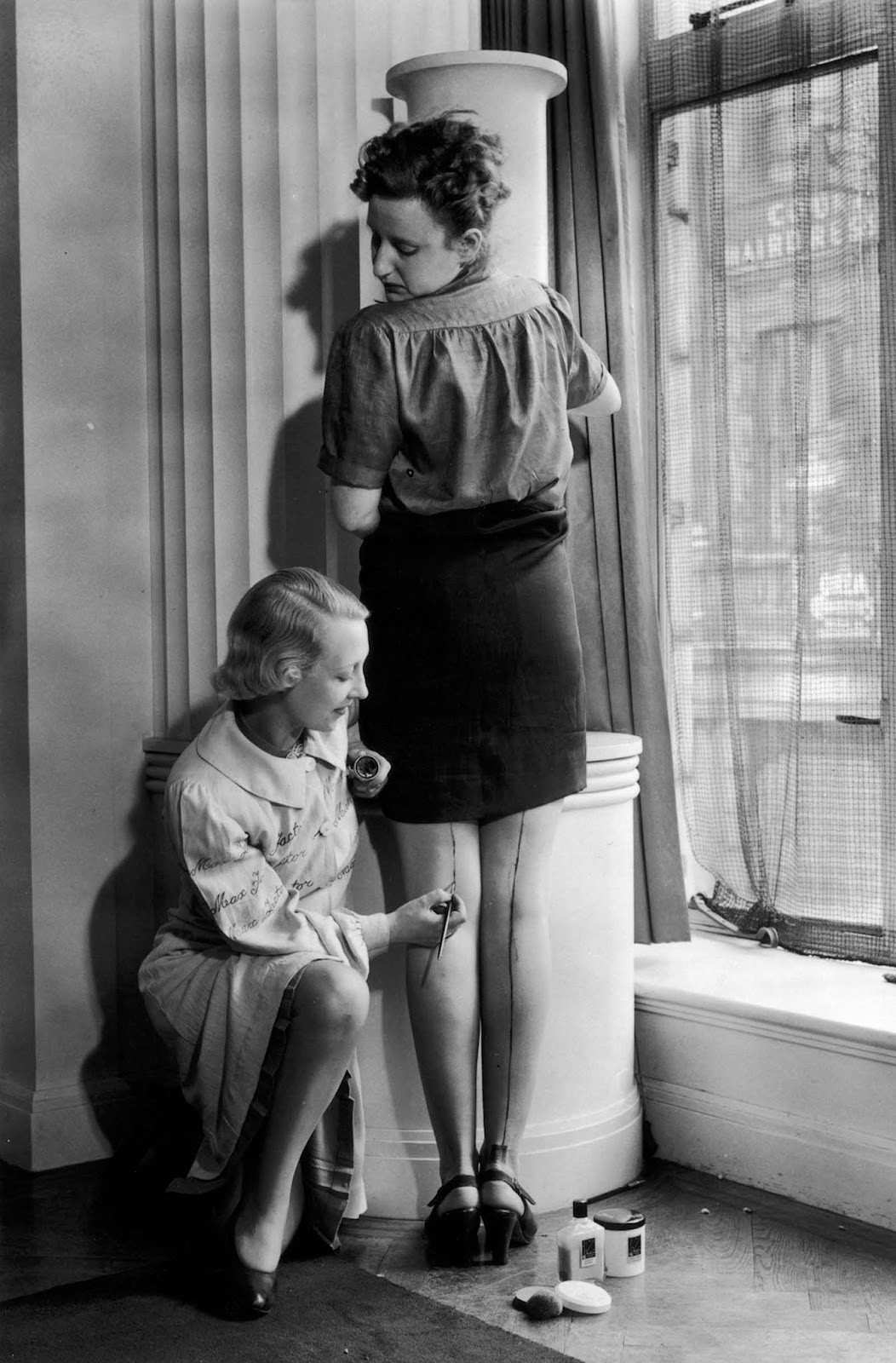A Max Factor beautician paints a seam on a woman's leg to help create the illusion of stockings.