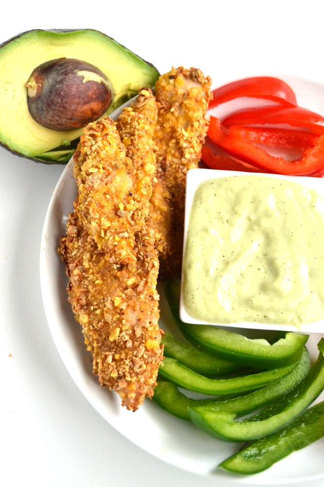 Baked Chicken Tenders with Avocado Jalapeno Dipping Sauce are a lighter take on typical chicken strips with a crunchy cereal breading that everyone will love! www.nutritionistreviews.com