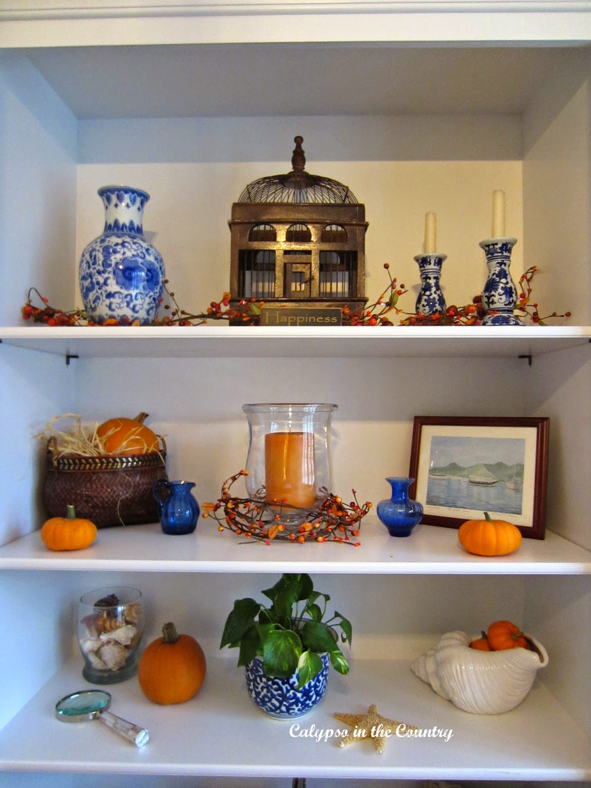 White Shelves decorated for fall with blue and orange