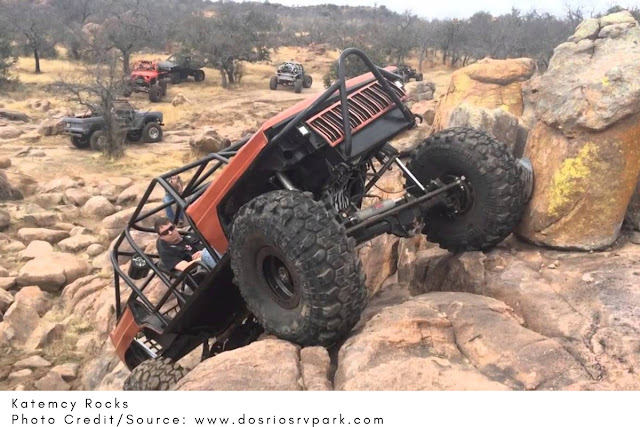 heavily modified XJ Jeep crawling up a steep pile of rocks