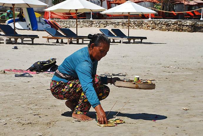 Mujer haciendo una ofrenda en la playa