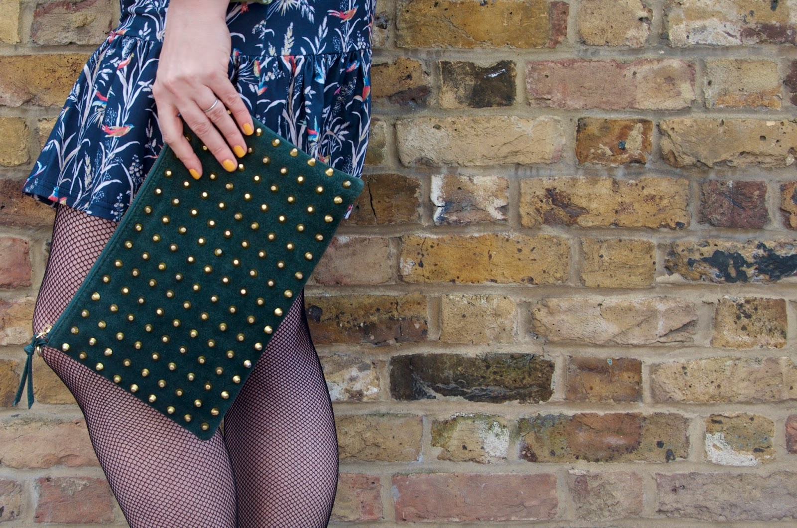 green studded clutch and fishnets