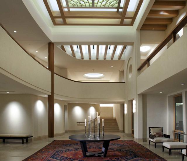 Desain dalam ruangan juga menggunakan bentuk melengkung dan dikombinasikan dengan material kayu pada tiang dan langit-langitnya.
