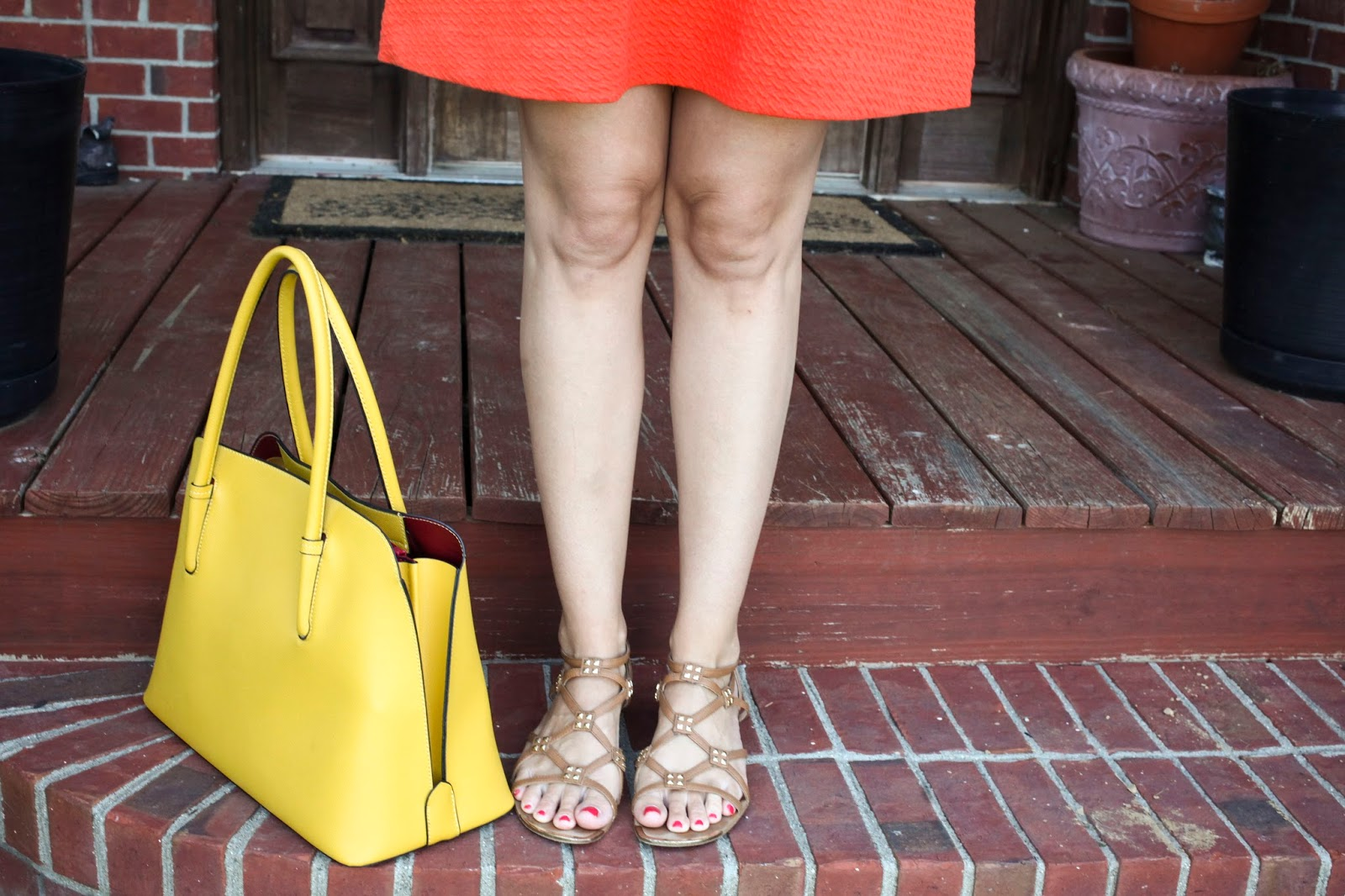 Yellow hand bag with orange dress and nude sandals