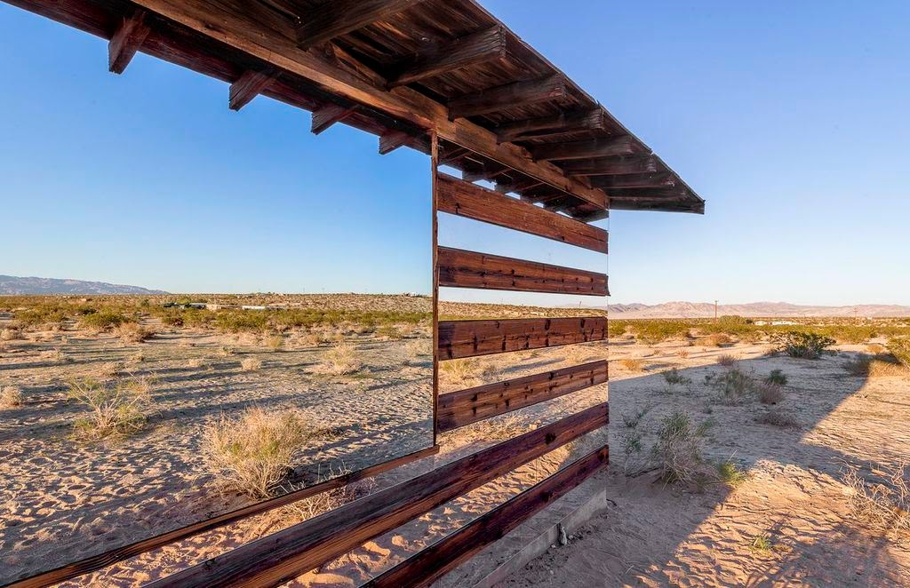 The effect almost makes the cabin appear invisible in places, playing tricks with light and the surroundings.- This Is What Happens When You Put Rows of Mirrors on a Shack in the Desert