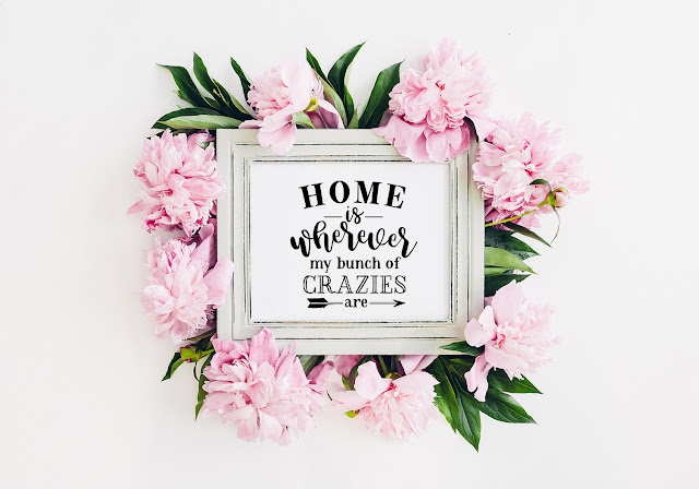 A framed print surrounded by flowers with the wording 'Home Is Where My Bunch Of Crazies Are'