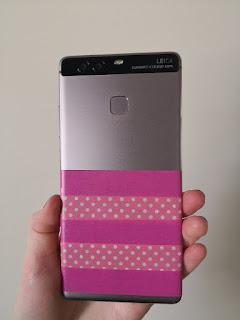 Kuva puhelimen takakannesta, joka on teipattu puoliksi pinkillä koristeteipillä.