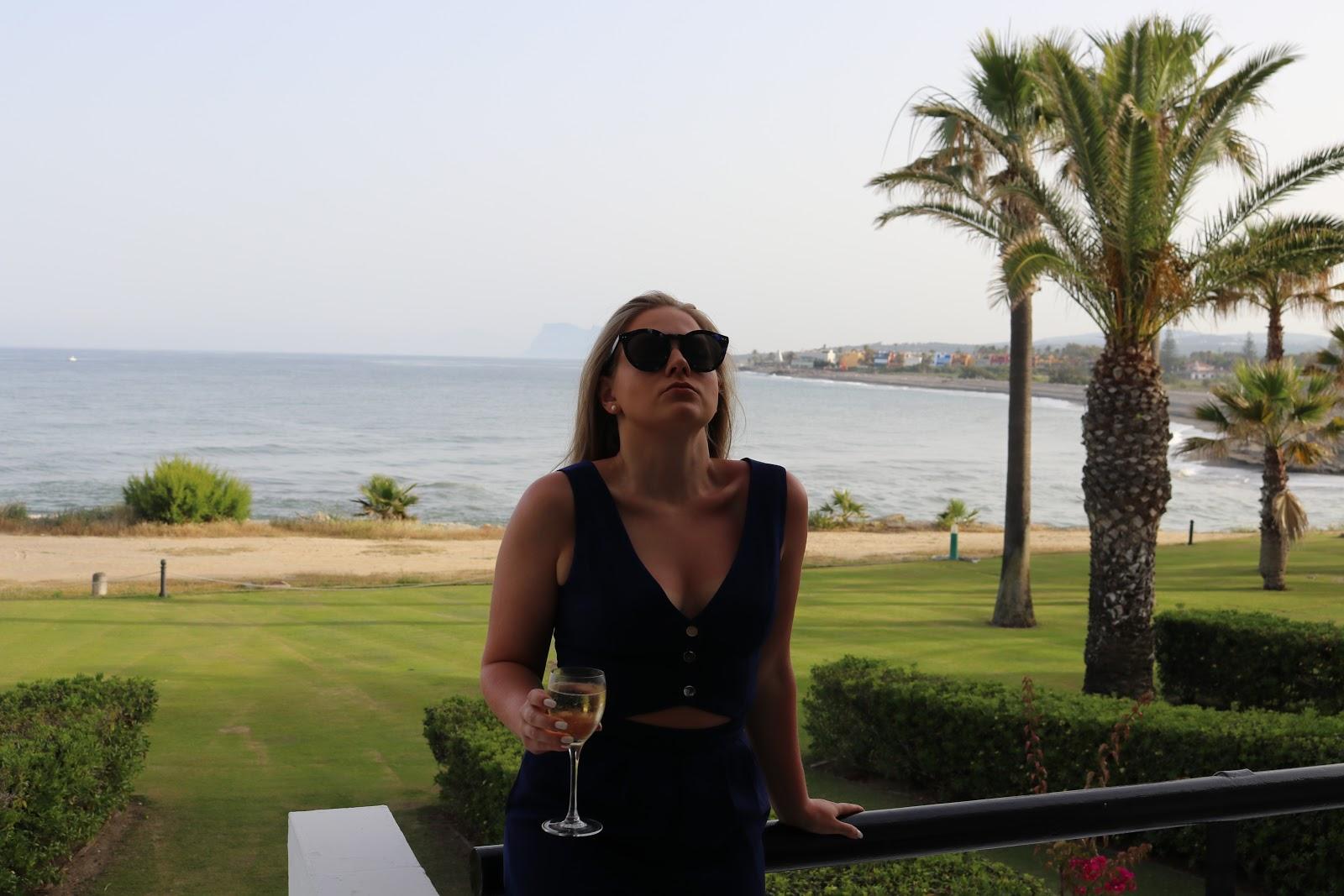 Blonde girl wearing Little Mistress blue jumpsuit, drinking a glass of wine on a balcony in Sotogrande, Spain