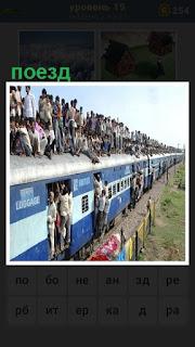 двигается поезд набитый людьми, в том числе на крыше люди