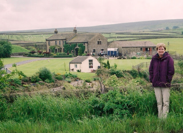 woman in front of stone farmhouse and stone fences in Yorkshire, England