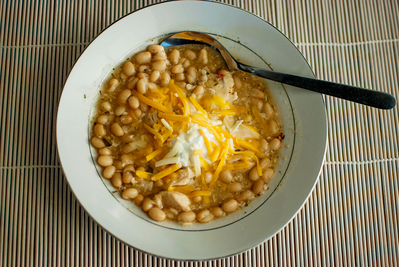 Bowl of White Bean Chicken Chili With Sour Cream and Shredded Cheese in a white bowl