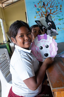 A Young Cambodian Girl holding up her creaton, a Poodle Mask