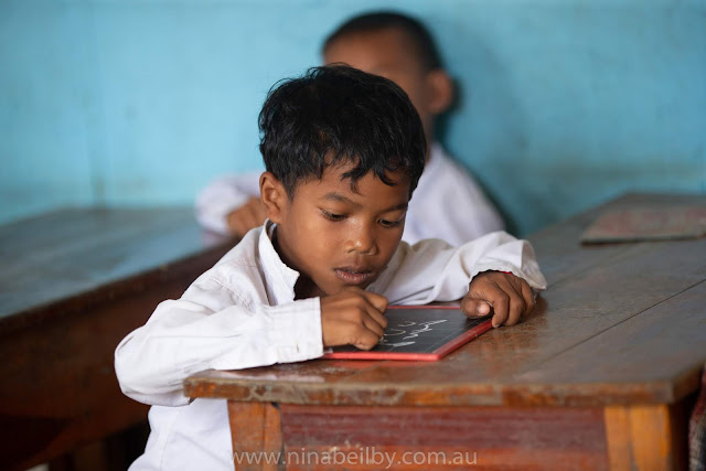A young male Cambodian student writing his letters onto a personal blackboard at his desk