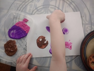 Toddler creating a space scene with potato stamps.