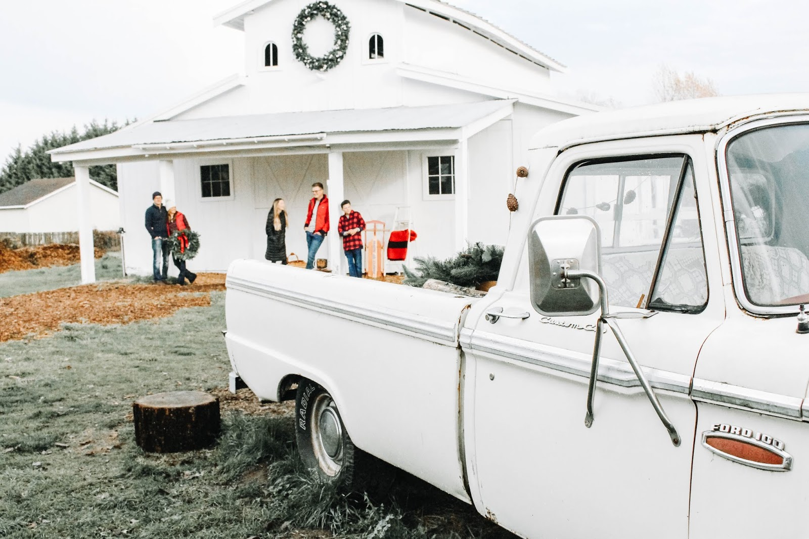 family christmas photos by a white barn with an old truck