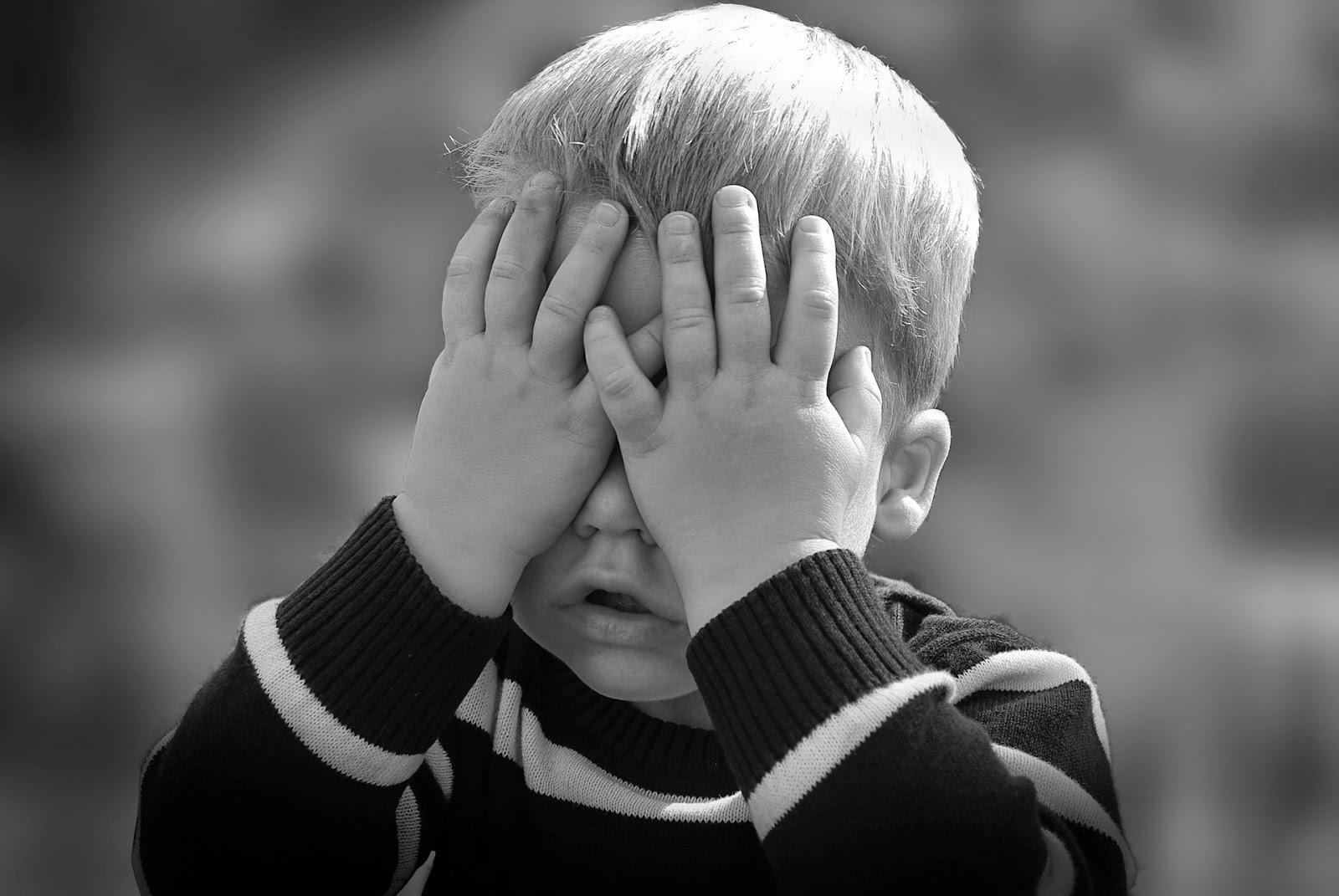 Kind schlägt Hände vor dem Gesicht zusammen