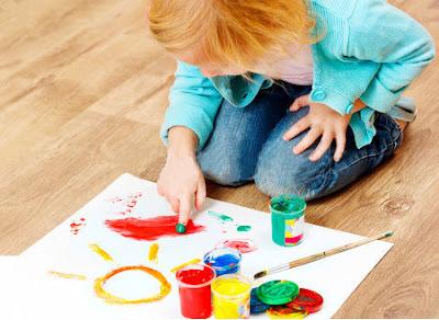 Рыжеволосая девочка рисует солнышко