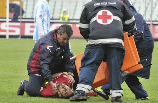Livorno player Piermario Morosini is helped by doctors as he lies on the pitch