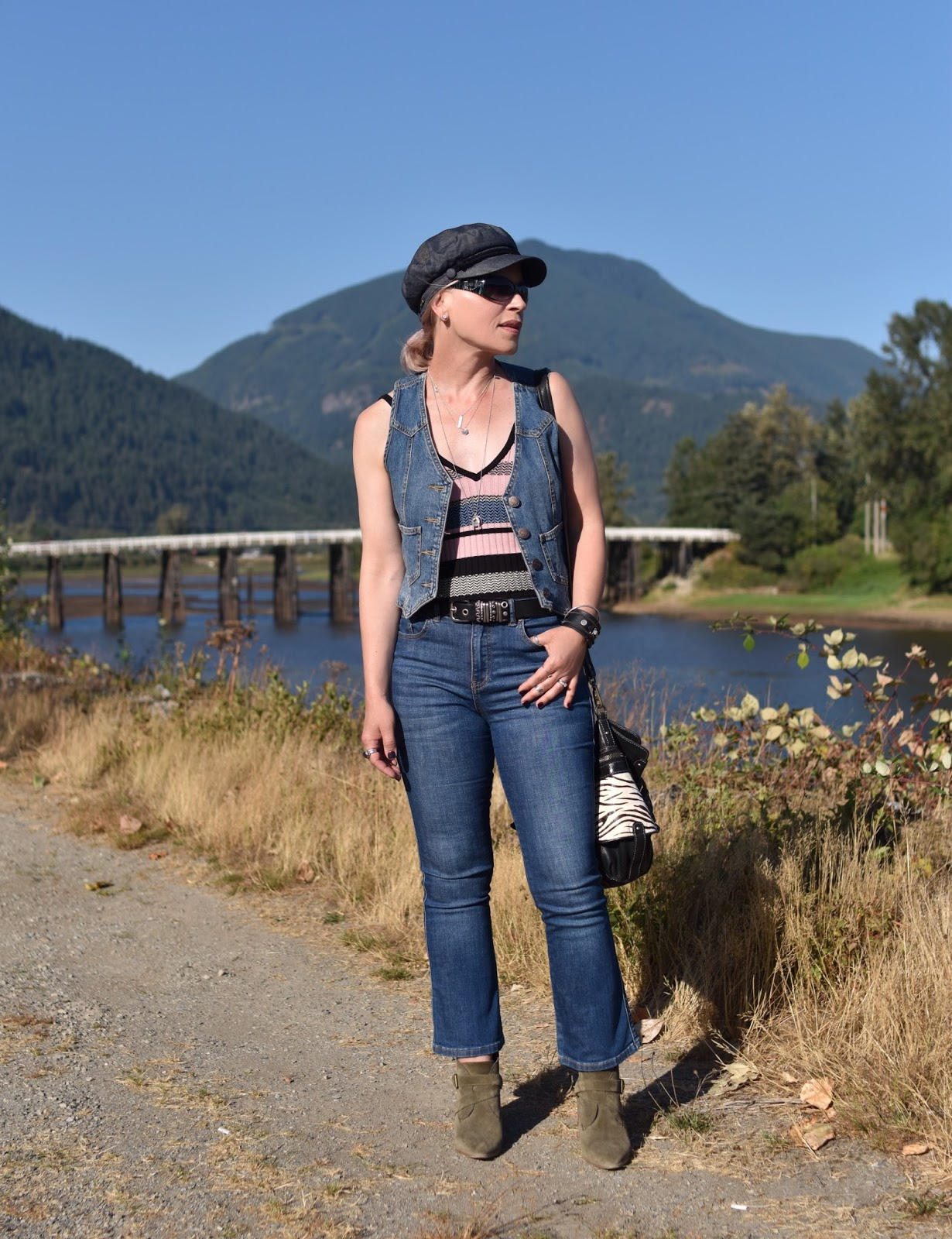 Monika Faulkner outfit inspiration - cropped flare jeans, striped tank top, denim vest, ankle boots, and a baker boy cap