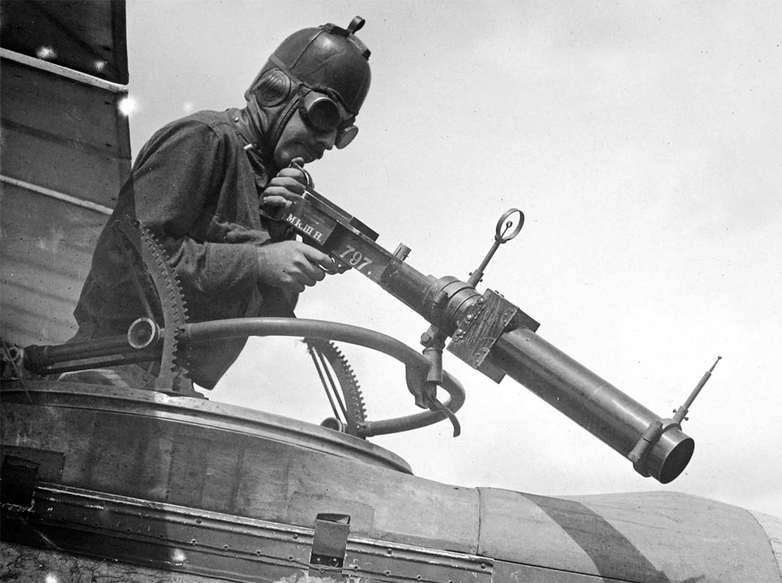 A soldier poses with a Hythe Mk III Gun Camera during training activities at Ellington Field, Houston, Texas in April of 1918. The Mk III, built to match the size, handling, and weight of a Lewis Gun, was used to train aerial gunners, recording a photograph when the trigger was pulled, for later review, when an instructor could coach trainees on better aiming strategies.