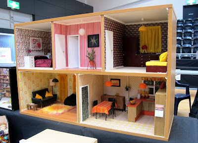Modern dolls' house miniature 1970s-style house in a bookcase.