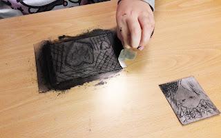 A mão de uma aluna a retirar a fita cola que prende o seu trabalho de monotipia à secretária