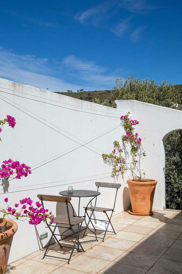 terraza con muebles de forja y paredes blancas