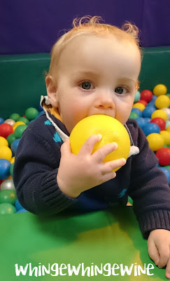 Smaller toddler eating a ball from the ball pit. Yum.