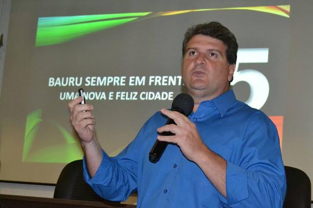 Foto de Clodoaldo Gazzeta, prefeito eleito em Bauru, durante campanha. Clodoaldo está com camisa azul, segurando um microfone numa mão e atrás dele uma slide com o slogan de sua campanha (Bauru sempre em frente: uma nova e feliz cidade).