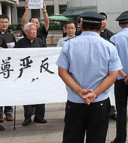 Mons. Vicente Weifang Zhu (centro) manifesta contra o governo comunista