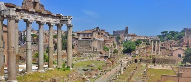 Vistas desde el mirador junto al Campidoglio sobre el Foro Romano con el Templo de Saturno y al fondo el Coliseo en Roma