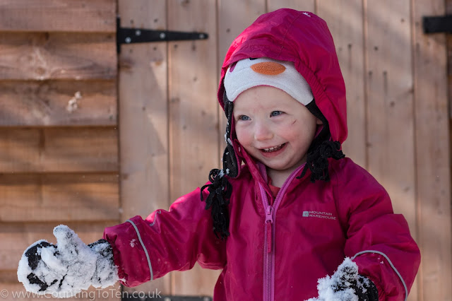 A toddler in a pink snow suit and penguin hat with very snowy gloves