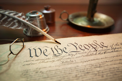 image of the Constitution, an old quill, set of glasses and ink well