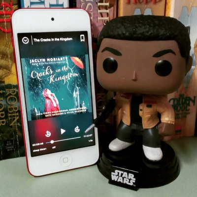 A Funko bobblehead of Finn from Star Wars stands next to a white iPod with Cracks In the Kingdom's cover on its screen, The cover features a white girl wearing a red cloak as she stands in a blue-tinged, rain-drenched open space. An orange umbrella blows away far above her. The iPod leans against the same set of books as in the above photo.