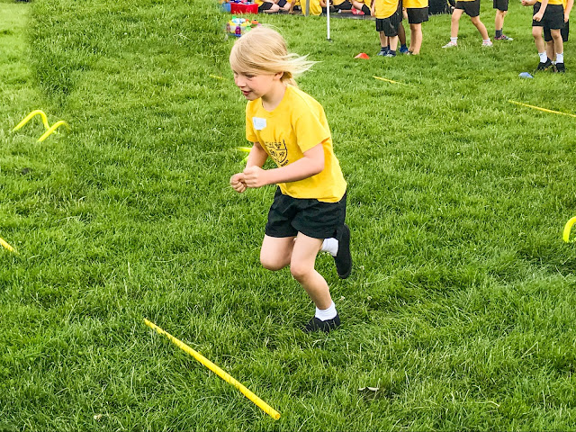A young girl running in a hurdles race over small yellow bits of plastic