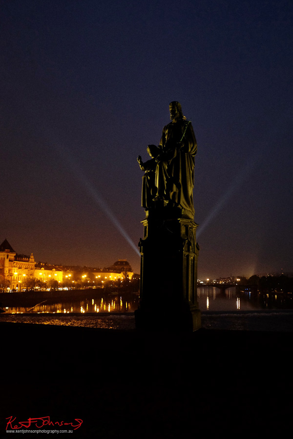 Back-lit statue of Saint Joseph at night.  The Charles Bridge in Spring Prague by Travel and Lifestyle Photographer Kent Johnson.