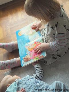 Geschwisterliebe: Kleinkind liest Baby vor