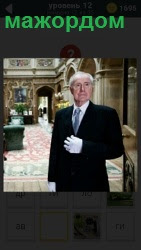 В помещении стоит мужчина мажордом в белых перчатках
