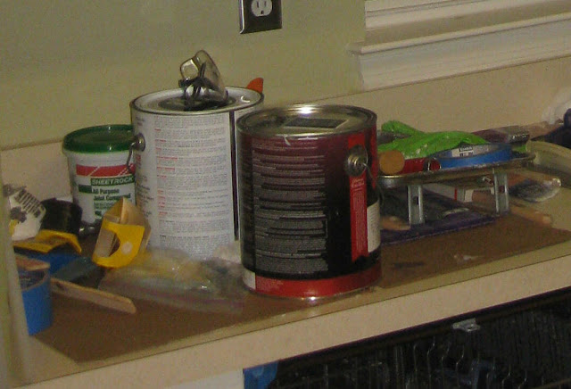 kitchen counter full of paint supplies for a makeover