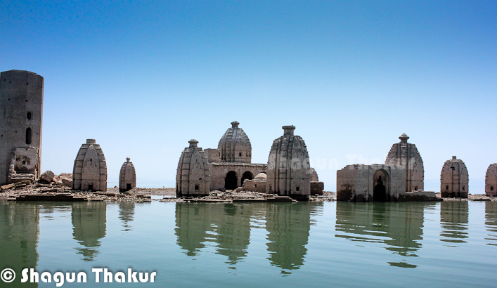 Here is a Photo Journey of Bathu Temples in Kangra region of Himachal Pradesh. Photo Journey is shared by Shagun Thakur, who belongs to this part of the state. Bathu temples can only be seen during summers as the water-level goes down in Pong Dam. Let's start the Photo Journey to Bathu Temples, with some interesting information about the place..First two photographs are clicked when water level is not at the peak, otherwise all the temples take a dip inside the Pong Dam Lake. Only some part of a huge pillar remain outside the water-levelBathu Temples are three kilometres away from Dhameta, which is a small town in Kangra. There stands a cluster of antique, unique, tall temples which remain dipped in water for most of the time in an year. Finally temples are exposed during months of March  to  June. Lot of pilgrims visit these temples during this time. Throughout the year, this place, commonly known as 'Bathu ki Larhi'  (a string of Bathu stone-structures) enjoys the unique distinction of being  a popular tourist spot.Shagun shared that Bathu Temples were build by Pandavas and were accessible by all the folks before Pong Dam was built. Earlier beas used to flow on it's side and temple was accessible throughout the year. Before Pong Dam was built, this cluster of unique artistic temples used to attract pilgrims from different parts of the country. At that time, there was only the  flowing Beas water near temples and no dam water engulfed  them as it does today. It was in 1961 that the work of Pong Dam started, giving it the final shape in 1970. The pillar on the left is the one which can be sensed during high water-level conditions :)Pong dam, now  occupies the vast stretch of land falling within the boundaries  of Terris , Dhameta , Bharmad, Jawali, Nagrota Suriyan, Dada-Sibha and Dehra. Pong Dam carries water of the Beas and those of the rivulets of Gajj, Vool and BundeirBathu ki Larhi is a cluster of eight  temples covering a vast area which used to have strong  pr