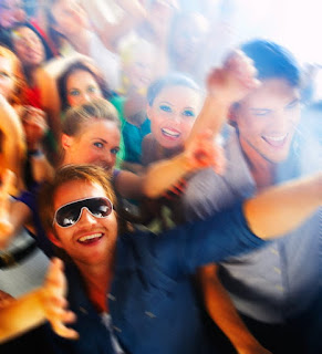Man with white rimmed sunglasses surrounded by happy people