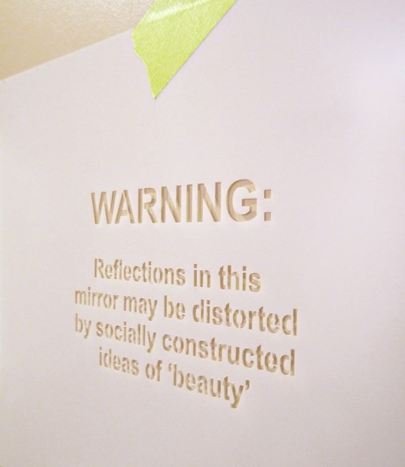 Feminist warning stenciled on mirror