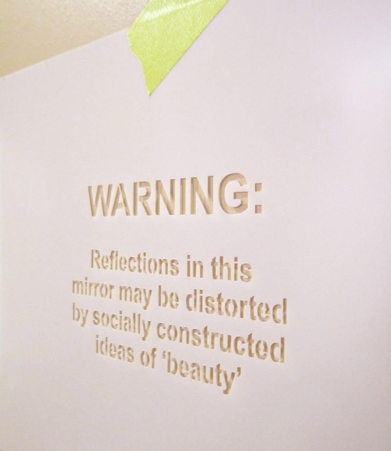 Feminist warning stenciled on mirror