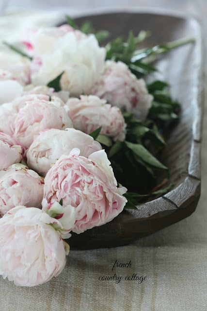 dough bowl on table with peonies inside